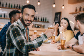 Photo selective focus of smiling man looking at camera while holding glass of beer