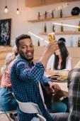 vidám afro-amerikai férfi nézi a kamerát, miközben a gazdaság pohár sör közelében multikulturális barátok