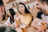 szelektíven középpontjában a fiatal ázsiai nő, aki üldögél ülve barátaival pub