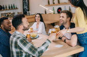 cheerful multicultural friends talking while drinking beer in pub
