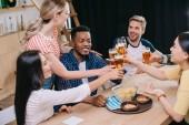fröhliche multikulturelle Freunde klinken Gläser von leichtem Bier in der Kneipe