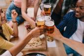Fotografie oříznutý pohled multikulturních přátel cinčení brýlí z lehkého piva v hospodě