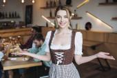 Fotografie schöne Kellnerin in deutscher Tracht blickt in die Kamera und zeigt Willkommensgeste