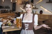 attraktive Kellnerin in deutscher Tracht, die einen Becher Leichtbier in der Hand hält und in die Kamera blickt