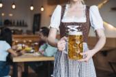patial Ansicht der Kellnerin in deutscher Nationaltracht halten Becher mit leichtem Bier