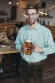 pohledný mladý muž držící džbánek lehkého piva a usmíval se na kameru