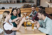 happy, young multicultural friends celebrating octoberfest together in pub