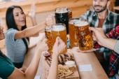 vidám barátok csengő bögre sört, miközben ünnepli Octoberfest pub