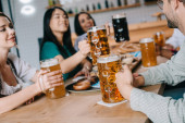 young multicultural friends drinking light and dark beer while celebrating octoberfest in pub