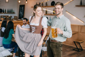 glückliche Männer und Frauen in Tracht mit Bierkrügen