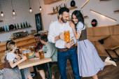 schöner junger Mann mit einem Glas Bier, während er neben einer attraktiven Frau in traditioneller deutscher Tracht steht