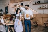 fröhlicher junger Mann mit einem Glas Bier beim Tanzen mit einer attraktiven Frau in traditioneller deutscher Tracht