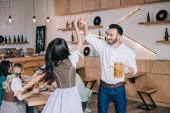 Fotografie glücklicher junger Mann hält Glas Bier beim Tanzen mit jungen Frau in traditionellen deutschen Kostüm