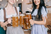 beschnittene Ansicht von zwei jungen Kellnerinnen in traditionellen deutschen Kostümen, die Becher mit Bier halten