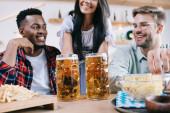 Fotografie abgeschnittene Ansicht der Kellnerin in traditioneller deutscher Tracht, die Bier für multikulturelle Freunde in der Kneipe serviert