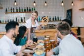 fröhliche Kellnerin in traditioneller deutscher Tracht hält Brezel, während sie in der Nähe von Freunden in der Kneipe steht