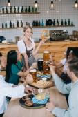 Fotografie fröhliche Kellnerin in traditioneller deutscher Tracht hält Brezel, während sie in der Nähe von multikulturellen Freunden steht, die das Oktoberfest in der Kneipe feiern