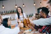schöne Kellnerin in Tracht neben multikulturellen Freunden, die Oktoberfest in Kneipe feiern
