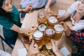 Teilansicht multikultureller Freunde, die Krüge mit hellem und dunklem Bier klappern