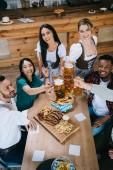 schöne Kellnerinnen in traditioneller deutscher Tracht, die mit multikulturellen Freunden Bierkrüge klappern