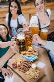 Fotografie selektiver Fokus attraktiver Kellnerinnen in traditionellen deutschen Kostümen, die Bierbecher mit multikulturellen Freunden klirren
