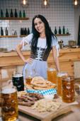 Fotografie schöne junge Kellnerin in traditionellen deutschen Kostüm halten Hand auf Hüfte und lächelnd in die Kamera