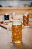 messa a fuoco selettivo di tazza con birra lager sul tavolo di legno in pub