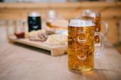 szelektív hangsúlyt a bögre a lager sör a fa asztal közelében tálca snack pub