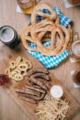 Draufsicht auf Bratwürste, Zwiebelringe, Pommes, Brezeln und Bierkrüge auf Holztisch im Wirtshaus