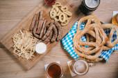 Draufsicht auf Becher mit hellem und dunklem Bier, Bratwürsten, Zwiebelringen, Pommes und Brezeln auf Holztisch im Wirtshaus