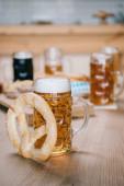 messa a fuoco selettivo di tazza con birra lager e pretzel sul tavolo di legno in pub