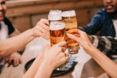 nyírt kilátás a multikulturális barátok klinking szemüveg lager sör pub