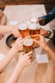 Fotografie částečný pohled na multikulturní přátele cintelé brýle s lagerovou pivem v hospodě