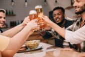 a vidám, multikulturális barátok, a sörözőben lévő lager sör részleges nézete