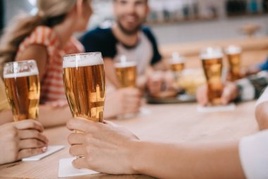 cropped view of women holding glasses of light beer while sitting together with friends in pub