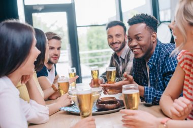 cheerful multicultural friends talking while sitting together in pub