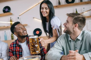 beautiful waitress in traditional german costume serving beer for multicultural friends in pub
