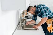 Fotografie Selektiver Fokus eines gutaussehenden bärtigen Reparateurs, der in der Nähe der Spüle in der Küche arbeitet