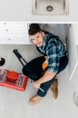 Photo top view of bearded handyman sitting on floor near toolbox and tools