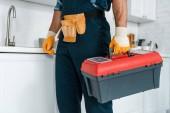 Ausgeschnittene Ansicht des Arbeiters in Uniform stehend und Werkzeugkiste haltend