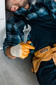 oříznutý pohled na vousatý pracovník přidržitelný klíč při práci v kuchyni