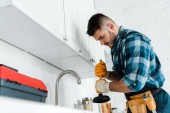 Photo selective focus of repairman holding plunger in kitchen
