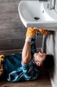 Photo selective focus of handyman fixing water damage in bathroom