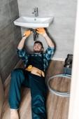 pohledný opravák, který opravuje poškození vody pomocí nastavitelného klíče v koupelně
