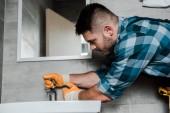 Fotografie pohledný vousatý opravák stojící blízko dřezu a v koupelně se dotýkal kohoutku