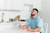 dühös ember gesztjáró ülve asztal közelében a konyhában
