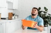 nelibě muž držící plastovou misku na mytí v kuchyni