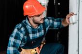 Fotografia lavoratore barbuto nel casco di sicurezza toccando interruttore della luce