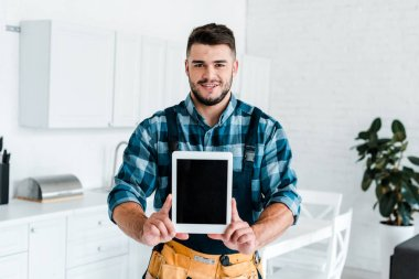 happy handyman holding digital tablet with blank screen