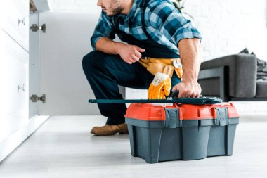 Cropped view of bearded handyman sitting and holding toolbox stock vector